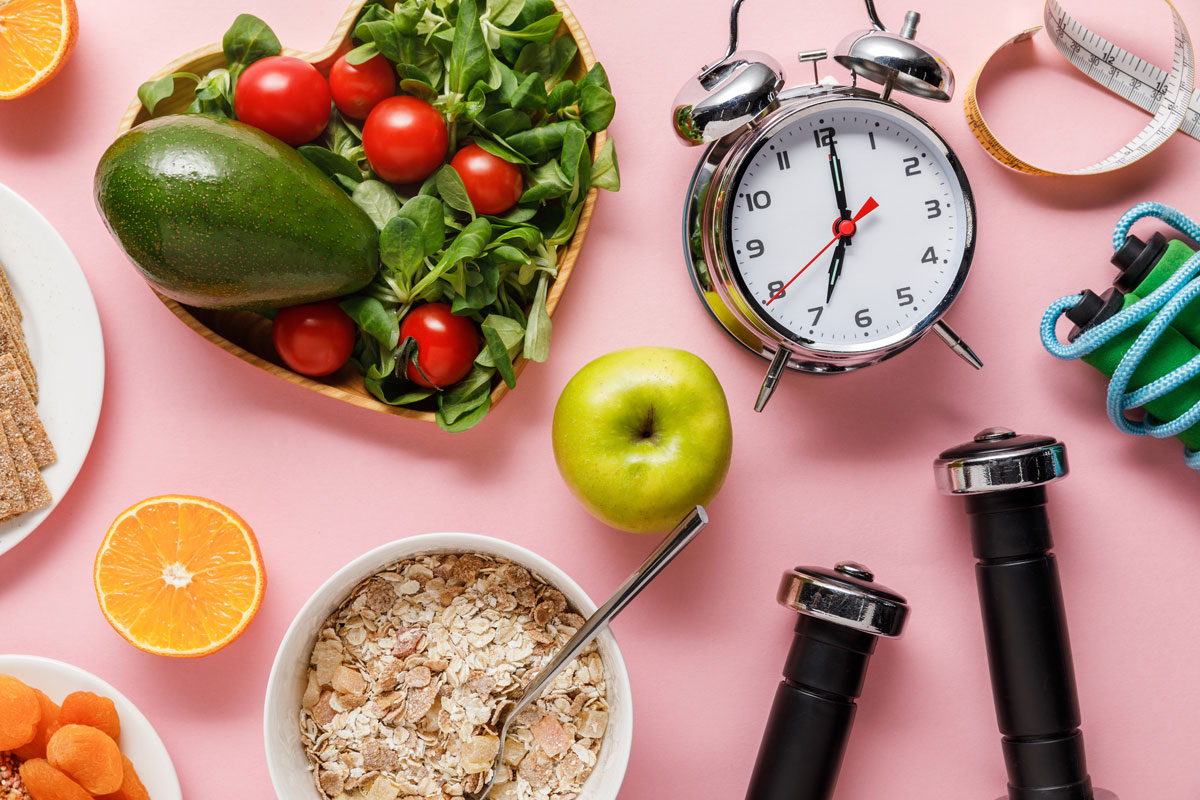 top view of fresh diet food, measuring tape, sport equipment and alarm clock on pink background